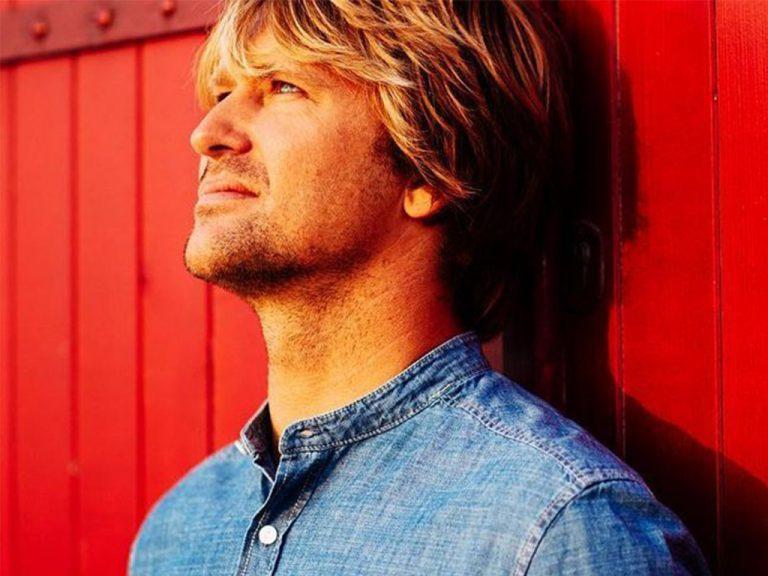 Portrait de profil de Tom Frager fond rouge